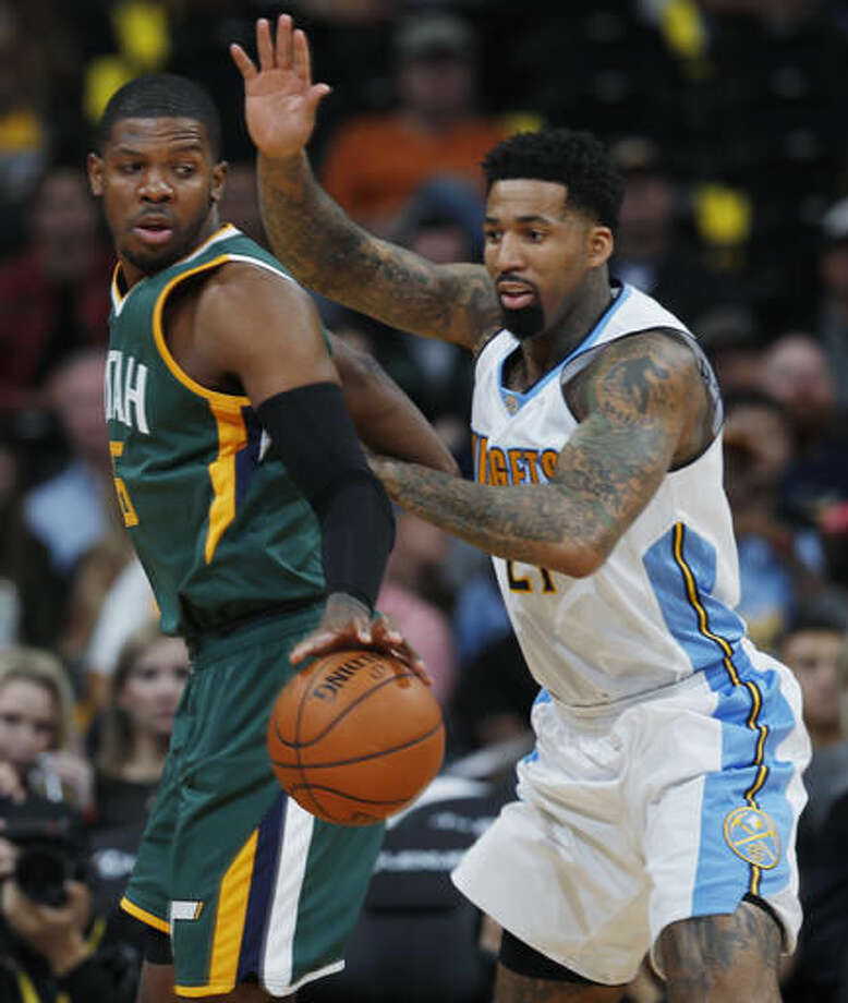 Utah Jazz forward Joe Johnson, left, reaches back to pick up a loose ball as Denver Nuggets forward Wilson Chandler defends in the first half of an NBA basketball game Sunday, Nov. 20, 2016, in Denver. (AP Photo/David Zalubowski)