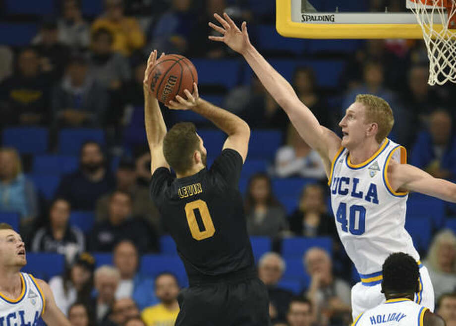 UCLA's Thomas Welsh (40) challenges a shot by Long Beach State's Gabe Levin (0) during the first half of an NCAA college basketball game in Los Angeles, Sunday, Nov. 20, 2016. (AP Photo/Michael Owen Baker)