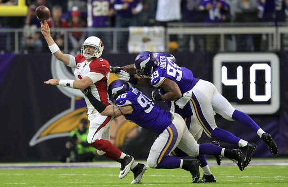 Arizona Cardinals quarterback Carson Palmer passes while getting pressured by Minnesota Vikings defenders Brian Robison (96) and Danielle Hunter (99) during the second half of an NFL football game Sunday, Nov. 20, 2016, in Minneapolis. (AP Photo/Andy Clayton-King)