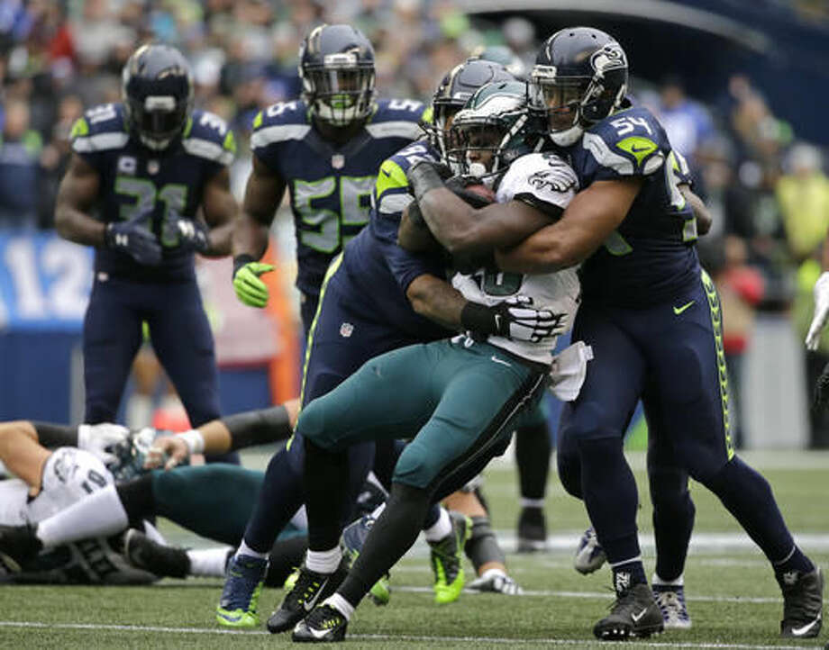 Philadelphia Eagles running back Wendell Smallwood is wrapped up by Seattle Seahawks middle linebacker Bobby Wagner, right, and defensive tackle John Jenkins in the first half of an NFL football game, Sunday, Nov. 20, 2016, in Seattle. (AP Photo/John Froschauer)
