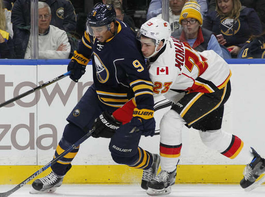 Buffalo Sabres forward Evander Kane (9) and Calgary Flames center Sean Monahan (23) battle for the puck during the first period of an NHL hockey game, Monday, Nov. 21, 2016, in Buffalo, N.Y. (AP Photo/Jeffrey T. Barnes)