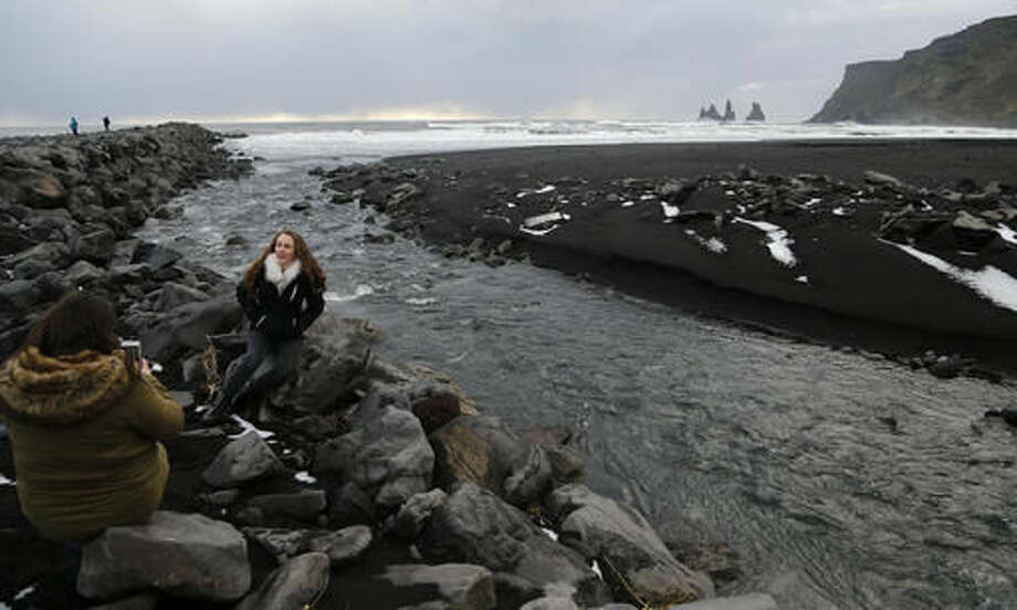 People sit on rocks at the black sanded beach in Vik, Iceland, near the Volcano Katla, Wednesday, Oct. 26, 2016. Katla Volcano has helped turn sleepy Vik, a community of 300 people some 110 miles (180 kilometers) east of the capital, Reykjavik, into a tourism hotspot. (AP Photo/Frank Augstein)