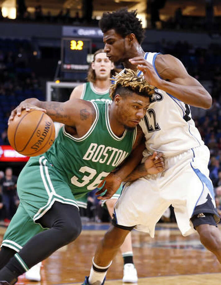 Boston Celtics' Marcus Smart, left, drives into Minnesota Timberwolves' Andrew Wiggins in the first quarter of an NBA basketball game, Monday, Nov. 21, 2016, in Minneapolis. (AP Photo/Jim Mone)
