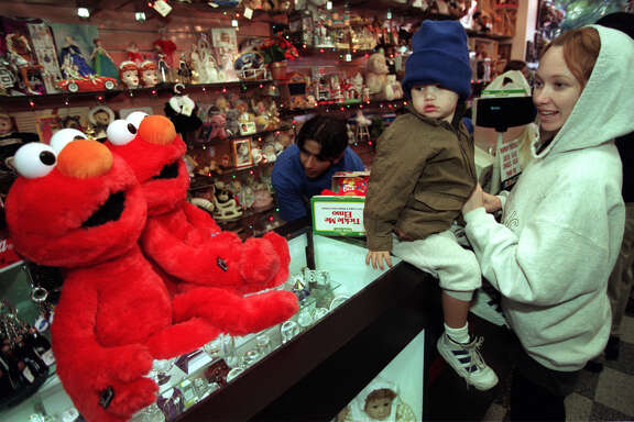 December 1996: 2-year-ol Nicholas Barrientos of Culver City and mother, Kristine, check out large Elmos sitting on toy store counter while clerk rings up their Tickle Me Elmo Friday morning. They were among some 50 folks lucky enough to have their lottery ticket drawn for opportunity to purchase the popular doll.  (Photo by Ken Lubas/Los Angeles Times via Getty Images)