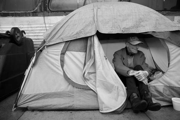 Kathy Gray takes shelter from the rain as she sits at the entrance to her tent along 13th Street on Friday, January 22, 2016 in San Francisco, Calif.