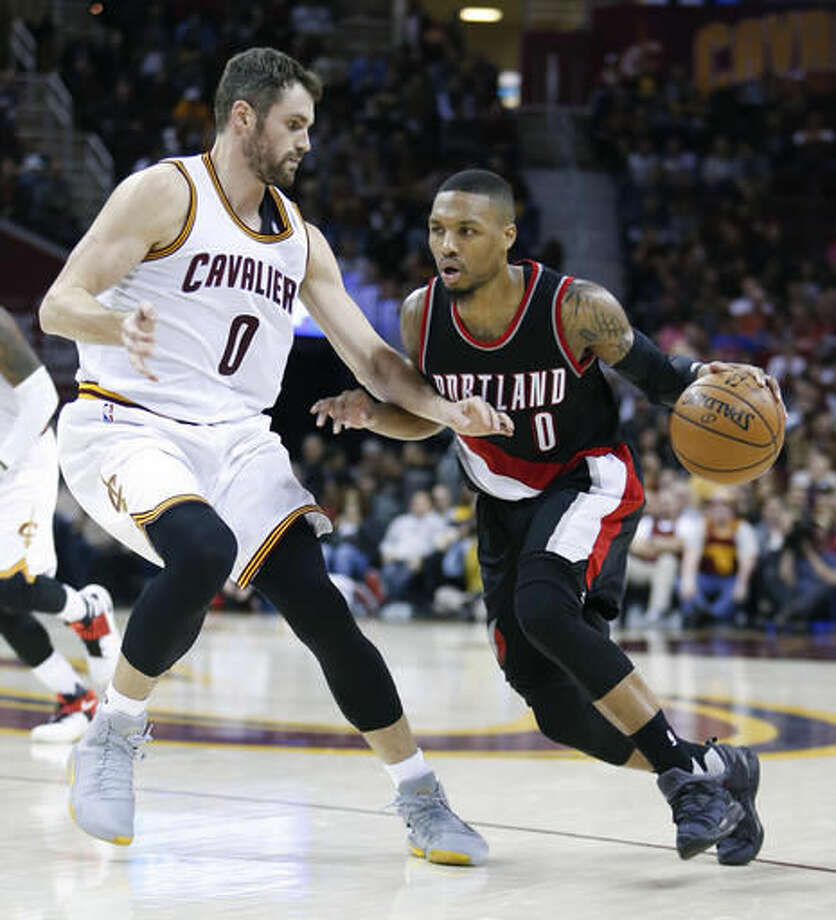 Portland Trail Blazers' Damian Lillard (0) drives on Cleveland Cavaliers' Kevin Love (0) during the second half of an NBA basketball game, Wednesday, Nov. 23, 2016, in Cleveland. The Cavaliers won 137-125. (AP Photo/Ron Schwane)