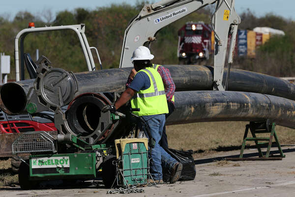 Workers move pipes Tuesday December 6, 2016 on the 8,000 block of Quintana Road where a large sinkhole formed at the ruptured junction of an old sewer pipe and a newer, wider pipe. Two cars were trapped in the 12-foot-deep hole resulting in the death of Doralinda Nishihara, a part-time Bexar County sheriff's deputy.