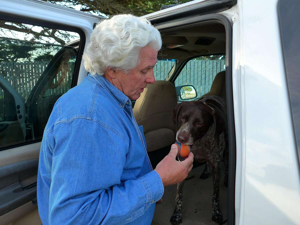 Randy Houston, founder and president of Purple Heart Anglers, plays with his dog Purple Heart Pennie in Half Moon Bay, CA, on Tuesday December 6, 2016.