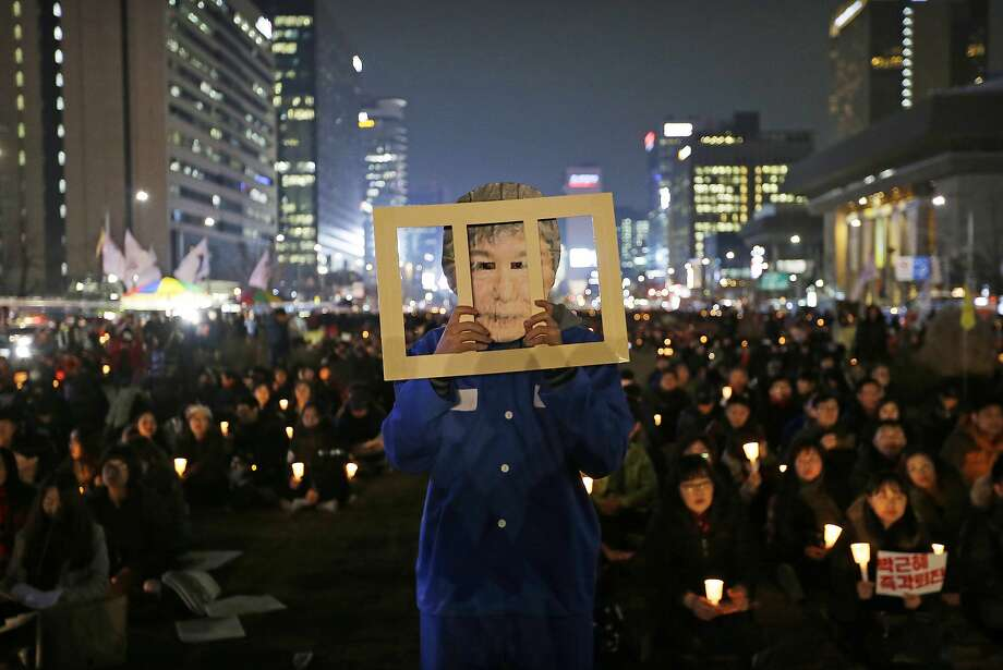 A protester late last month wears a mask of President Park Geun-hye during a rally calling for her impeachment in Seoul. Her opponents are struggling to set a date to strip her of power. Photo: Ahn Young-joon, Associated Press