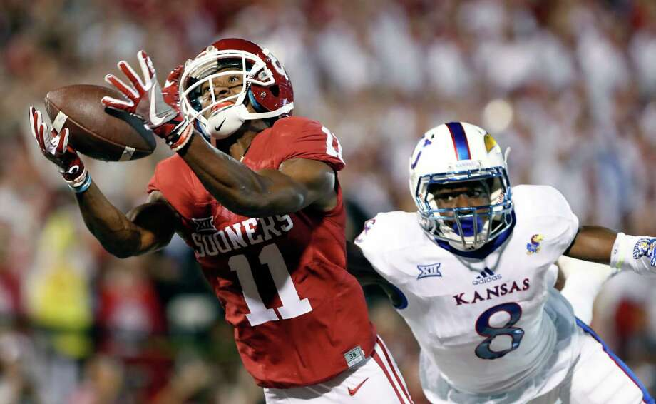 FILE - In this Oct. 29, 2016, file photo, Oklahoma wide receiver Dede Westbrook (11) makes a catch for a touchdown ahead of Kansas cornerback Brandon Stewart (8) during the first half of an NCAA college football game in Norman, Okla. Westbrook was selected Offensive Player of the Year for The AP All Big 12 team, Tuesday, Dec. 6, 2016. (AP Photo/Alonzo Adams, File) Photo: Alonzo Adams, FRE / FR159426 AP