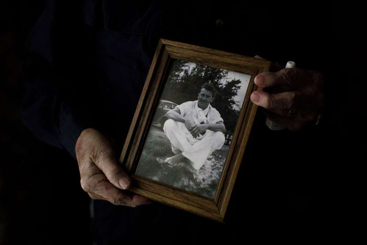 Virgil Lee Ward at his San Antonio home in 2016 holds a photo of himself when he joined the Army. Ward, one of a dwindling number of San Antonio Pearl Harbor Survivors, later moved to the Dallas area. He died Sunday at 102.