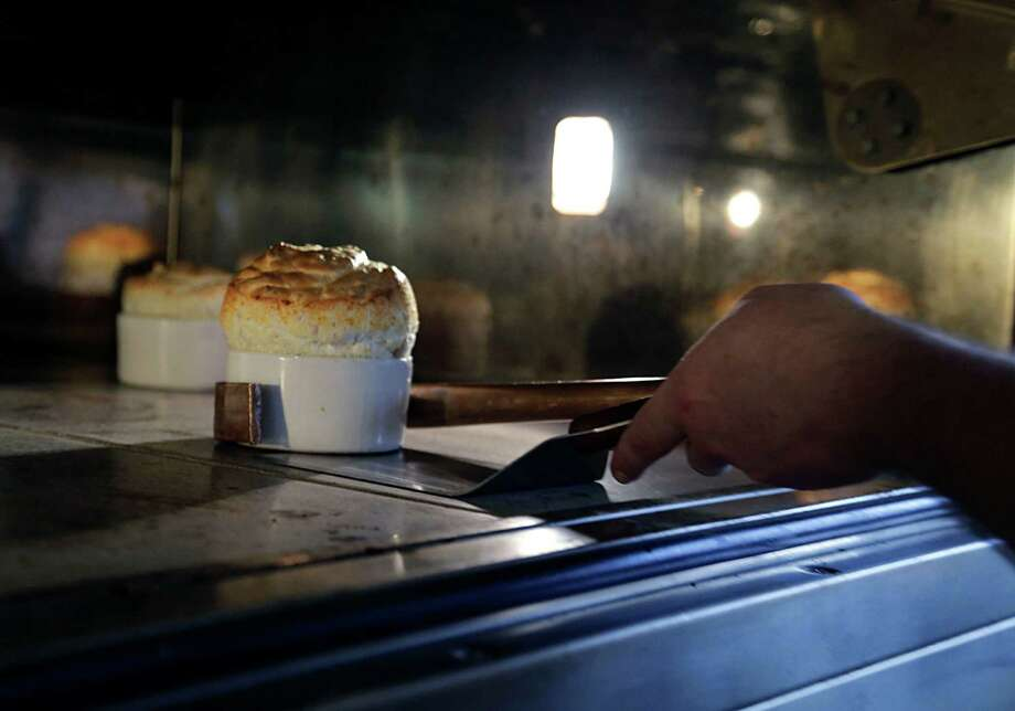 Chef Nicholas Alvis removes a soufflé from the oven at Rise No. 2. Founded by Hedda Gioia Dowd, the first Rise is located in Dallas. Photo: James Nielsen, Staff / © 2016  Houston Chronicle