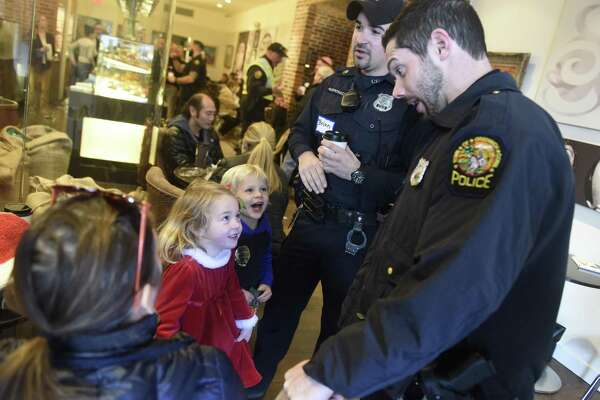 "Greenwich Police Officers Brian Andronaco, left, and Wally Wallace chat with 4-year-olds Olivia Bennett, of Riverside, and Callum Hennigan, of Old Greenwich, during the ""Coffee with a Cop"" event at Coffee Café Roasters in Greenwich."