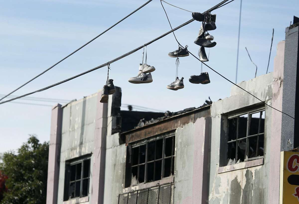 Pairs of shoes dangle from overhead wires in front of the Ghost Ship artist collective warehouse in Oakland, Calif. on Tuesday, Dec. 6, 2016 where at least 36 people died after a fire engulfed the building during an electronic music dance party Friday night.