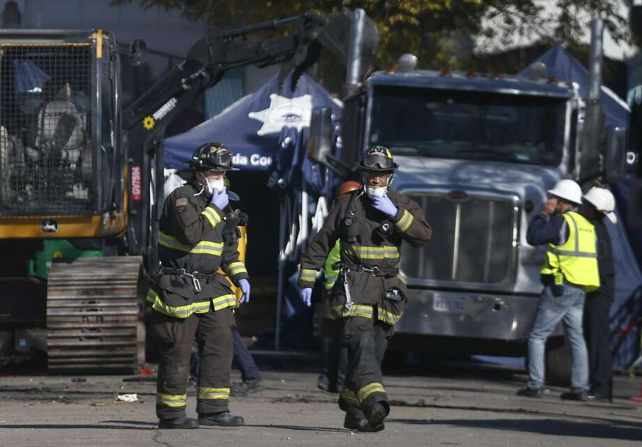 Firefighters remove protective masks on a break during the recovery operation after the blaze at an Oakland warehouse. Photo: Paul Chinn, The Chronicle