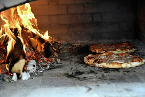 Pizzas bake in the outdoor pizza oven during a showcase for the School of Hotel, Culinary Arts and Tourism on Tuesday, Dec. 6, 2016, at Schenectady County Community College in Schenectady, N.Y. (Cindy Schultz / Times Union)