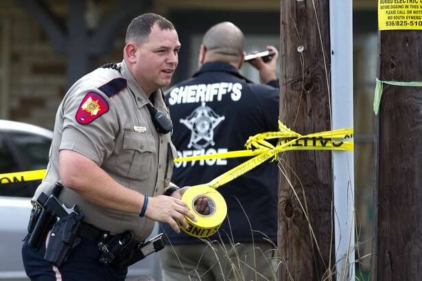 An officer with the Montgomery County Sheriff's Office tapped off a scene where several people were detained at a home on McCaleb Road near Texas 105 West following a robbery, which occurred shortly before 1 p.m. Tuesday, Dec. 6, 2016.