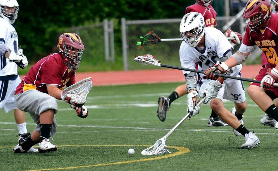 St. Joseph goalie Tim Izzo, left, looks to stop the ball before Staples' #20 Kip Orban can scoop it up near the goal, during boys lacrosse action in Westport, Conn. on Saturday May 22, 2010. Photo: Christian Abraham / Connecticut Post