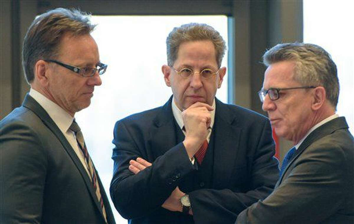 Hans-Georg Maassen, head of Germany's domestic intelligence service, center, listens to Interior Minister Thomas de Maiziere, right, and the head of Germany's Federal Criminal Police Office, BKA, Holger Muench, left, during a meeting of interior ministers of German federal states, in Saarbruecken, Germany, Wednesday Nov. 30, 2016. Germany's domestic intelligence service says an employee suspected of trying to pass along sensitive material to Islamic extremists had only been working for the agency for a short time. (Oliver Dietze/dpa via AP)