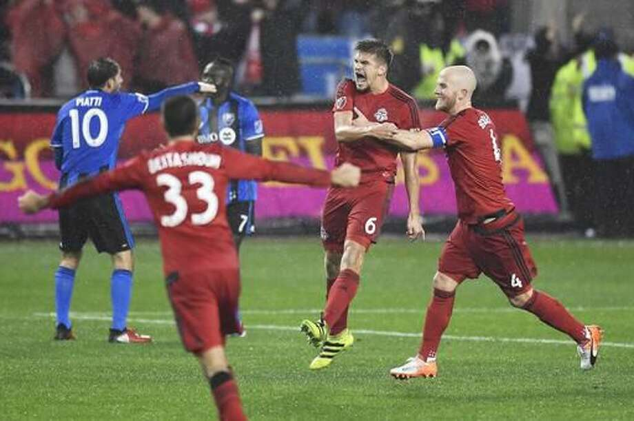 Toronto FC defender Nick Hagglund (6) celebrates his goal against the Montreal Impact with teammates Michael Bradley (4) and Steven Beitashour (33) during the second half of the second leg of MLS Eastern Conference championship series, in Toronto on Wednesday, Nov. 30, 2016. (Frank Gunn/The Canadian Press via AP)