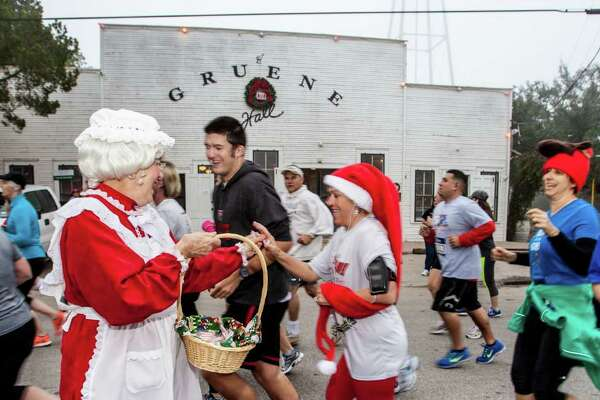 A festively attired volunteer hands out holiday stuff at the Jingle Bell Run/Walk in Gruene Historic District in New Braunfels.