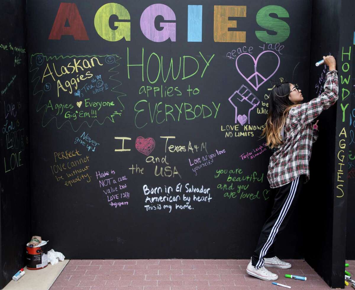 Texas A&M student Susana Magdalena Mata signs an Aggies United board calling for unity in the wake of a speech being held by White Nationalist Richard Spencer on the campus of Texa A&M University on Tuesday, Dec. 6, 2016, in College Station.