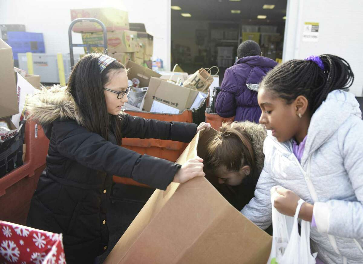 Fifth-graders Mia Chaux, left, Ashley Brusky, center, and Leah Orr sort donated food at the Food Bank of Lower Fairfield County on Tuesday, Dec. 6, 2016. Fourty-five fifth-graders from Julia Stark Elementary School came to the food bank Tuesday.