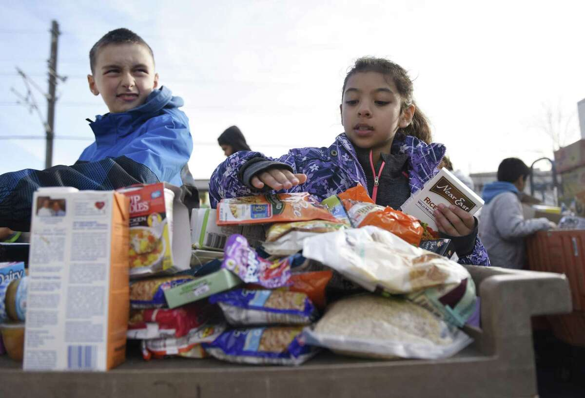 Fifth-graders Mergim Morina and Brianna Garcia sort donated food at the Food Bank of Lower Fairfield County in Stamford, Conn. Tuesday, Dec. 6, 2016. Fourty-five fifth-graders from Julia Stark Elementary School came to the food bank Tuesday to help sort and box donated food goods and watch a video about hunger and charitable food assistance. This event marked the culmination of the Stamford Public Education Foundation's 10-week service-learning mentoring program.