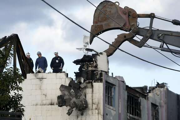 A recovery crew takes down a parapet on the Ghost Ship artist collective warehouse in Oakland, Calif. on Tuesday, Dec. 6, 2016 where at least 36 people died after a fire engulfed the building during an electronic music dance party Friday night.