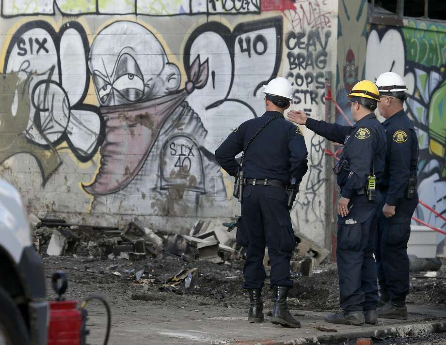 Sheriff's deputies working on the recovery operation stand in front of the Ghost Ship artist collective warehouse in Oakland, Calif. on Tuesday, Dec. 6, 2016 where at least 36 people died after a fire engulfed the building during an electronic music dance party Friday night. Photo: Paul Chinn, The Chronicle