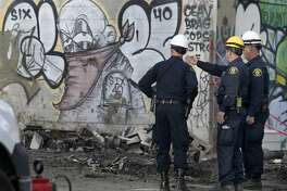 Sheriff's deputies working on the recovery operation stand in front of the Ghost Ship artist collective warehouse in Oakland, Calif. on Tuesday, Dec. 6, 2016 where at least 36 people died after a fire engulfed the building during an electronic music dance party Friday night.