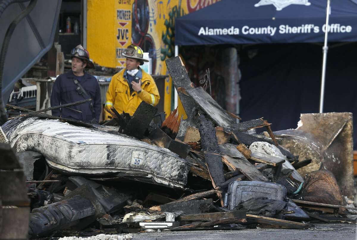 Firefighters work behind a pile of charred debris including a mattress removed from the Ghost Ship artist collective warehouse in Oakland, Calif. on Tuesday, Dec. 6, 2016 where at least 36 people died after a fire engulfed the building during an electronic music dance party Friday night.