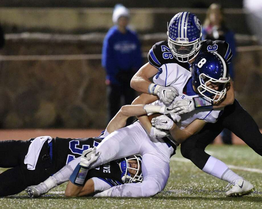 Darien defenders Timothy Herget (31) and Nicholas Green (26) team up for a tackle on Southington's Jack Herms (8) in the CIAC Class LL high school football semifinal game between No. 1 Darien and No. 4 Southington at Stamford High School's Boyle Stadium in Stamford, Conn. Monday, Dec. 5, 2016. Photo: Tyler Sizemore / Hearst Connecticut Media / Greenwich Time