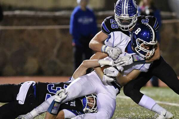Darien defenders Timothy Herget (31) and Nicholas Green (26) team up for a tackle on Southington's Jack Herms (8) in the CIAC Class LL high school football semifinal game between No. 1 Darien and No. 4 Southington at Stamford High School's Boyle Stadium in Stamford, Conn. Monday, Dec. 5, 2016.