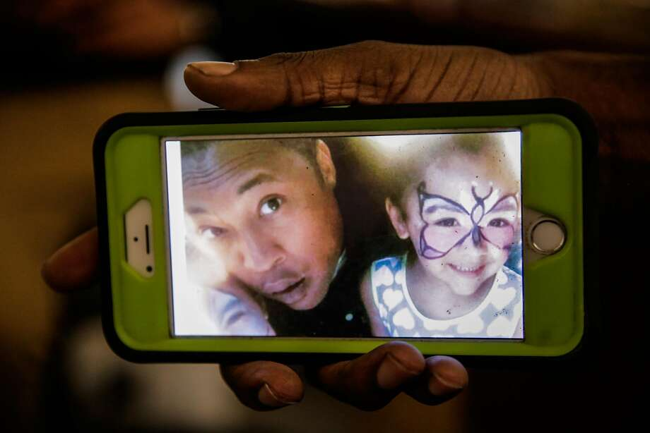 Kenzie Smith, 33, friend of Ghostship fire victim Alex Ghassan, holds a photo of his friend Alex pictured with Alex's daughter, during an interview at Captured Images Gallery and Framing  in Oakland, California, on Tuesday, Dec. 6, 2016. Photo: Gabrielle Lurie, The Chronicle