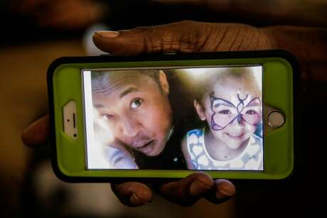Kenzie Smith, 33, friend of Ghostship fire victim Alex Ghassan, holds a photo of his friend Alex pictured with Alex's daughter, during an interview at Captured Images Gallery and Framing  in Oakland, California, on Tuesday, Dec. 6, 2016.