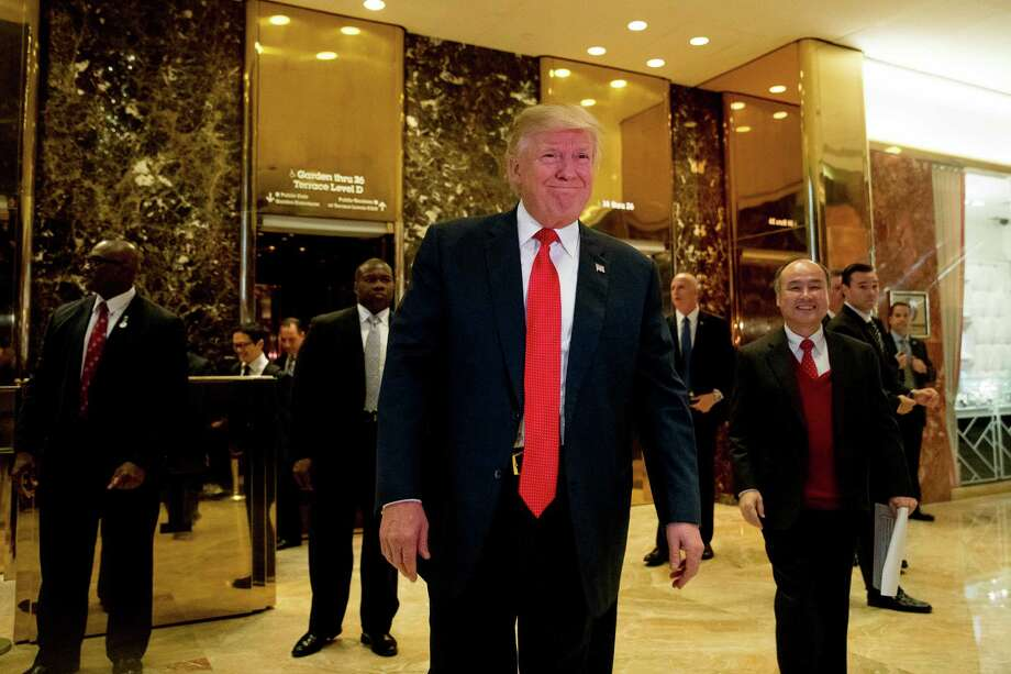 President-elect Donald Trump and SoftBank CEO Masayoshi Son, right, walk into the lobby to speak to members of the media at Trump Tower in New York, Tuesday, Dec. 6, 2016. (AP Photo/Andrew Harnik) Photo: Andrew Harnik, STF / Copyright 2016 The Associated Press. All rights reserved.