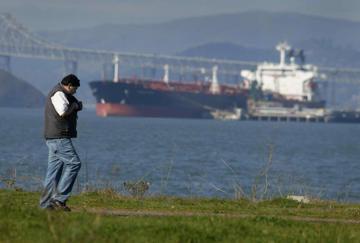 A man walks on a trail in front of an oil tanker docked at the Chevron refinery long wharf in Richmond, Calif. on Friday, Jan. 25, 2013.