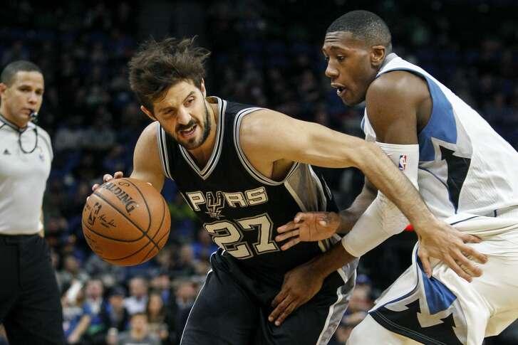 San Antonio Spurs guard Nicolas Laprovittola (27) tries to work arouind Minnesota Timberwolves guard Kris Dunn (3) in the second quarter of an NBA basketball game, Tuesday, Dec. 6, 2016, in Minneapolis. (AP Photo/Bruce Kluckhohn)