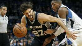 San Antonio Spurs guard Nicolas Laprovittola (27) tries to work arouind Minnesota Timberwolves guard Kris Dunn (3) in the second quarter of an NBA basketball game, Tuesday, Dec. 6, 2016, in Minneapolis. (AP Photo/Bruce Kluckhohn)