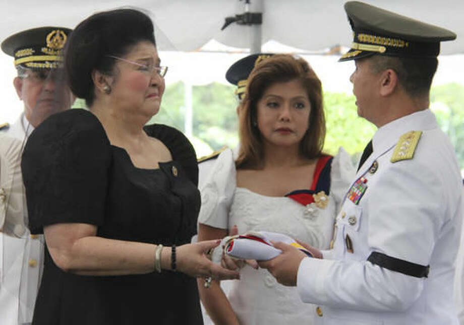 In this photo provided by the Office of the Army Chief Public Affairs Headquarters Philippine Army, Imelda Marcos, the widow of the late dictator Ferdinand Marcos, cries as she receives the Philippine flag from a military officer as their daughter Imee Marcos looks on during a ceremony of his burial at the Heroes' Cemetery in suburban Taguig city, Philippines, Friday, Nov. 18, 2016. Photo: HOGP