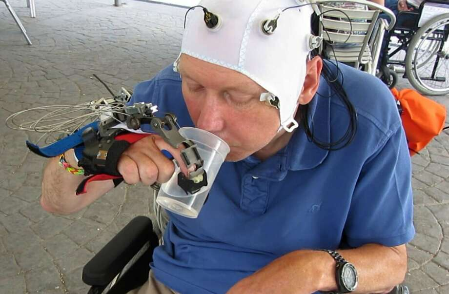 A patient whose motor skills are limited by a spinal injury uses a robotic hand to drink from a cup. Photo: Mario Cortese, Associated Press