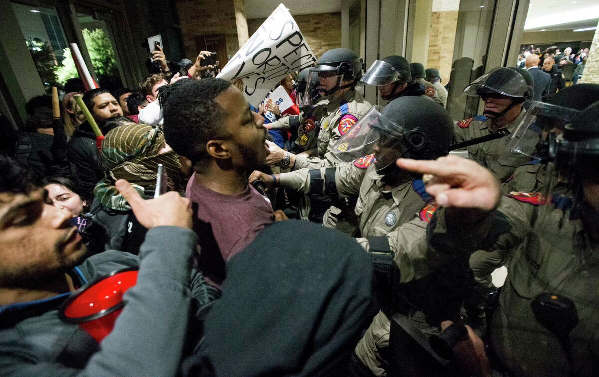 Law enforcement officers come face to face with protesters outside the Texas A&M Memorial Student Center on Tuesday.