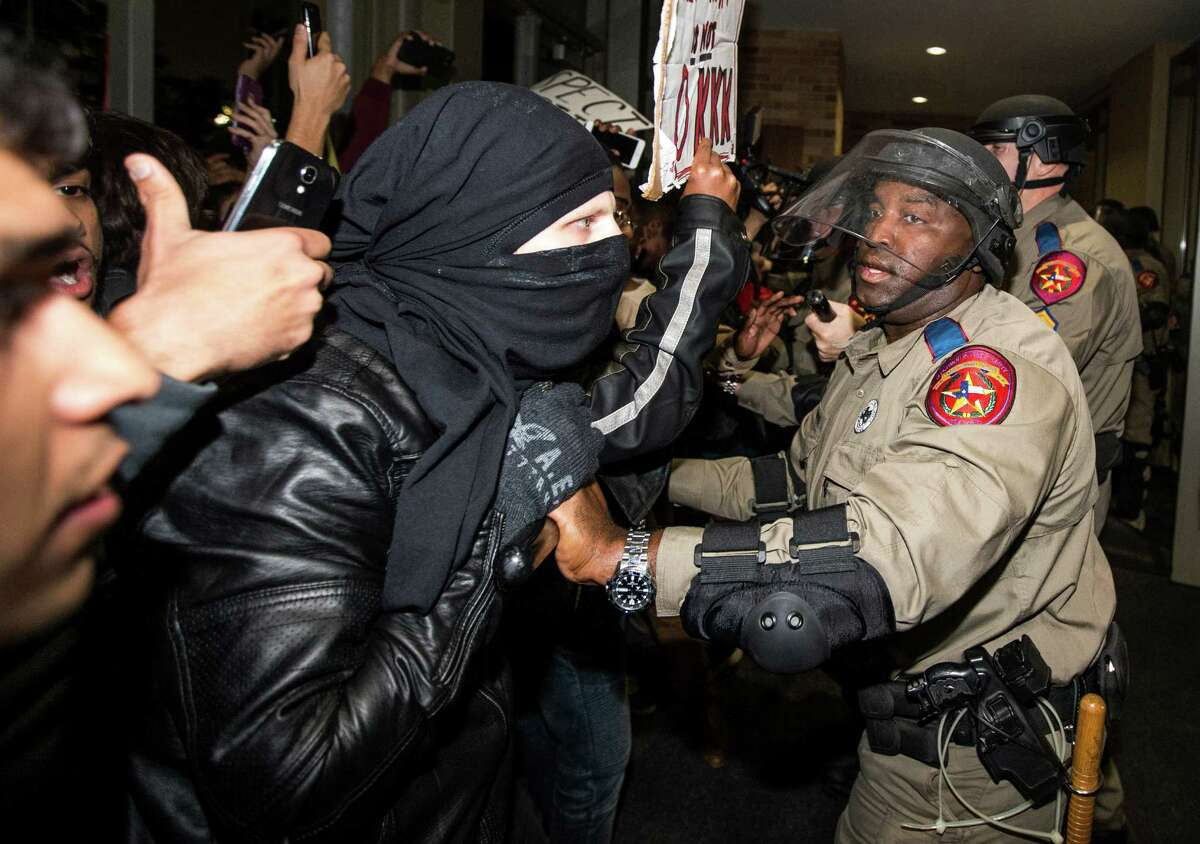Law enforcement officers face off with protesters outside the Texas A&M Memorial Student Center on Tuesday.