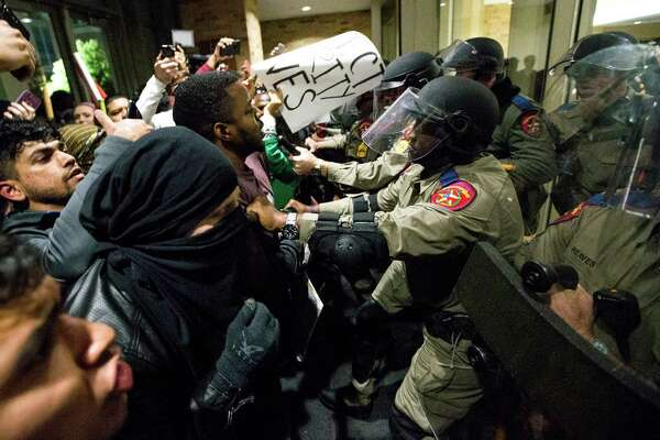 Law enforcement officers push protester out of the Texas A&M Memorial Student Center during a protest agaisnt a speech on campus by White Nationalist Richard Spencer on Tuesday, Dec. 6, 2016, in College Station.