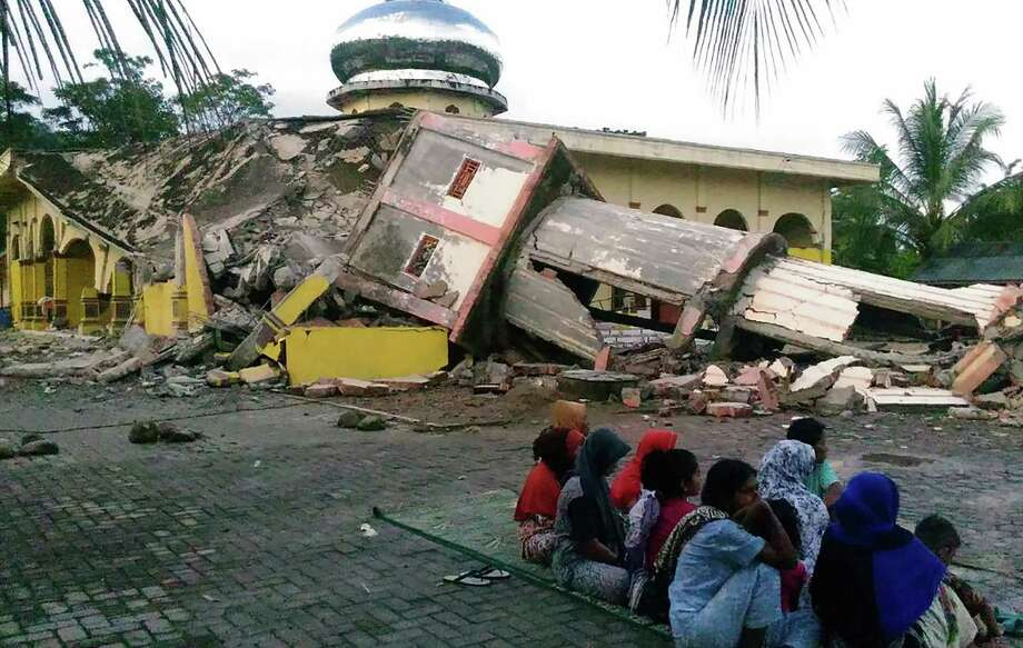 Residents gather outside a damaged mosque, its minaret reduced to rubble following its collapse, after a 6.5-magnitude earthquake struck the town of Pidie, Indonesia's Aceh province in northern Sumatra, on December 7, 2016. One person died and dozens were feared trapped in rubble after a strong earthquake struck off Aceh province on Indonesia's Sumatra island on December 7, officials said.  / AFP PHOTO / ZIAN MUTTAQIENZIAN MUTTAQIEN/AFP/Getty Images Photo: ZIAN MUTTAQIEN, Stringer / AFP or licensors