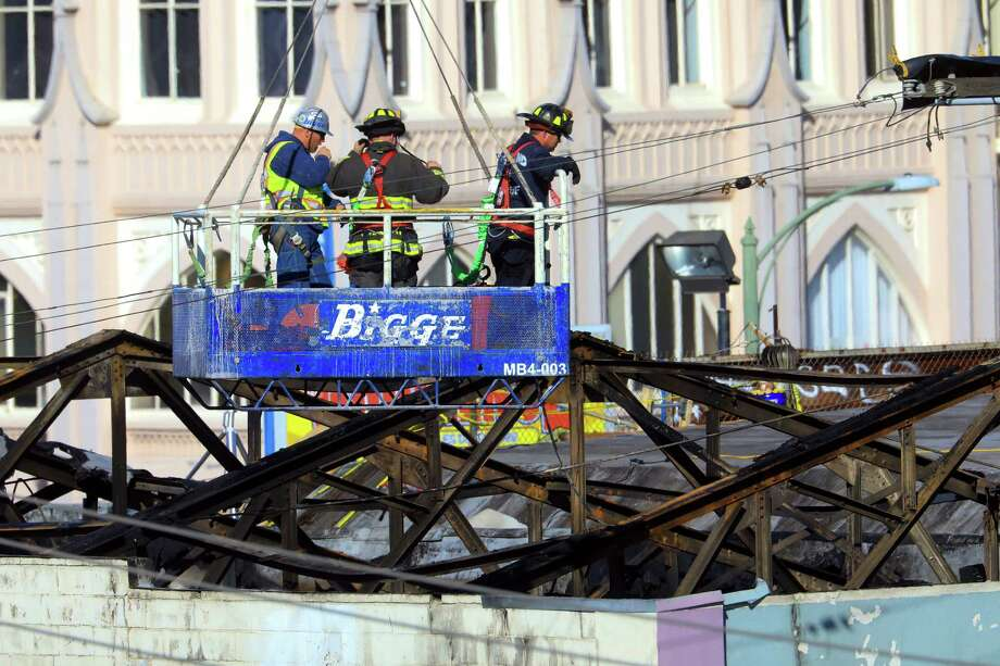 Firefighters and a worker are lifted on Tuesday by a crane into the remnants of the warehouse that burned in Oakland, Calif. The warehouse went up in flames last Friday, leaving at least 36 people dead, and was well-known to people who spent time there for being filled with illegal residences and potentially hazardous construction. Photo: JIM WILSON, STF / NYTNS