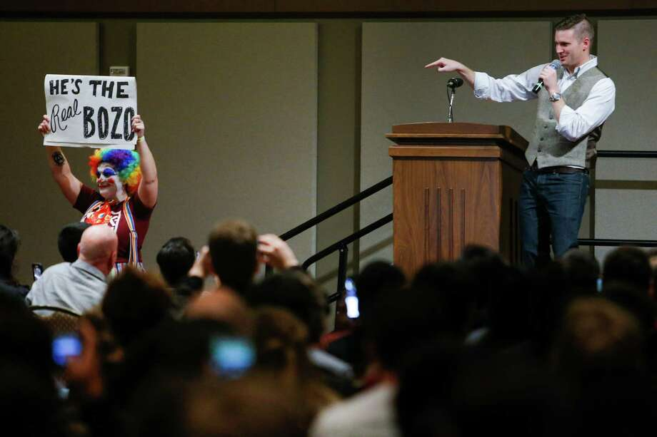 "White nationalist Richard Spencer points at a protestor dressed as a clown with a sign reading ""He's the real bozo"" who walked in front of the stage as he speaks at Texas A&M University Tuesday, Dec. 6, 2016 in College Station. Photo: Michael Ciaglo, Houston Chronicle / © 2016  Houston Chronicle"