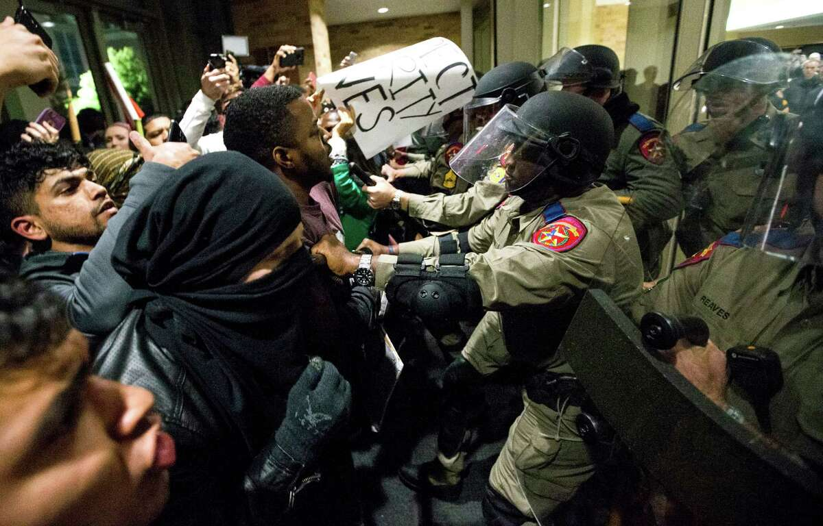 Law enforcement officers push protester out of the Texas A&M Memorial Student Center during a protest against a speech on campus by White Nationalist Richard Spencer on Tuesday, Dec. 6, 2016, in College Station.