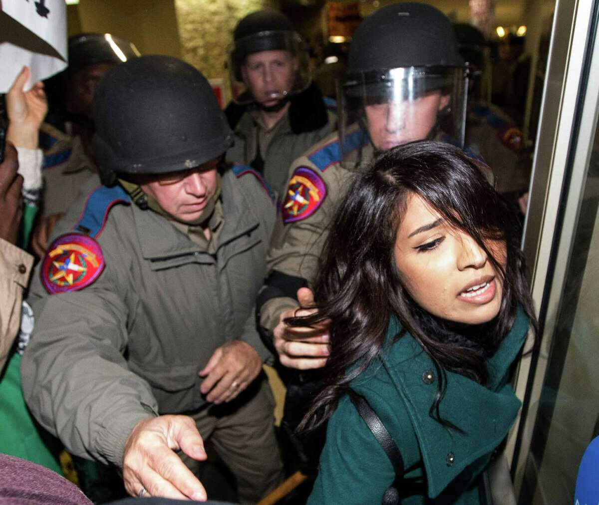A woman is taken into custody as law enforcement officers push protesters out of the Texas A&M Memorial Student Center during a protest against a speech on campus by White Nationalist Richard Spencer on Tuesday, Dec. 6, 2016, in College Station.